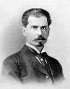 Photographie ancienne en noir et blanc, de trois quarts, du visage d'un homme portant une moustache et une barbe courte.