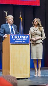 """Donald and Melania Trump standing behind a blond-wood podium with the words """"TRUMP"""", """"TEXT &squot;TRUMP&squot; TO 88022"""", """"MANCHESTER, New Hampshire"""", and """"MAKE AMERICA GREAT AGAIN"""" printed in white-on-blue text from top to bottom. Donald is to the left, behind the actual podium. Melania is about three feet to his left."""