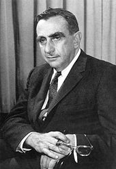 Head and shoulders of a man with bushy eyebrows.