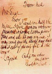 Lettres gribouillées sur une feuille de papier jaunie.