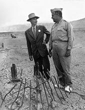 Un homme souriant en costume et un autre en uniforme autour d'une pile de métal tordu.