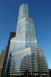 the Trump International Hotel and Tower, a tall steel Chicago skyscraper with aquamarine windows, as seen on a sunny day