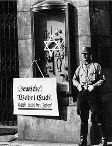 Photographie en noir et blanc d'un membre de la SA à côté d'une panneau appelant au boycottage des commerces juifs