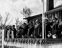 Hommes en costumes et uniformes debout sur une estrade décorée en train de saluer.