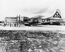 Un quadrimoteur étincelant se trouve sur la piste de décollage et son équipage prend la pose devant lui.