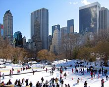 An outdoor skating rink with many people on the rink. There are skyscrapers in the background. This is the Wollman Rink in Central Park.