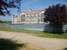 Photographie qui représente la construction d'un bâtiment avec un arbre sur le fond.