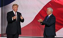 """Donald Trump and his running mate for vice president, Mike Pence, at the Republican National Convention in July 2016. They appear to be standing in front of a huge screen with the colors of the American flag displayed on it. Trump is at left, facing toward the viewer and making """"thumbs-up"""" gestures with both hands. Pence is at right, facing toward Trump and clapping."""