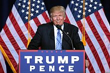 """Trump standing behind a brown wood podium with a sign bearing the words """"TRUMP PENCE"""" on a blue sign. There are two American flags behind his position."""