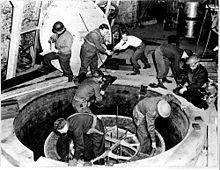 Soldats et ouvriers, dont certains portent un casque en acier grimpent hors de ce qui ressemble à un bouche d'égout géante.