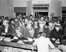 Nombreux ouvriers devant un comptoir à l'intérieur d'un bâtiment.