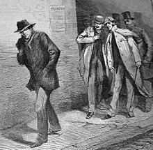 Dans une rue sombre, un homme portant un chapeau s'éloigne vers la gauche sous les regards de quatre hommes se tenant debout à la droite.