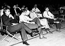 A group of men in shirtsleeves sitting on folding chairs.