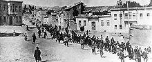 Une colonne de personnes encadrée par des hommes en armes à la sortie d'une ville.