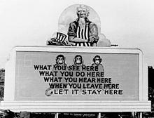 Oncle Sam a posé son chapeau et remonte ses manches. Sur le panneau situé en dessous de lui se trouvent les trois singes de la sagesse et le slogan: What you see here / What you do here / What you hear here / When you leave here / Let it stay here.