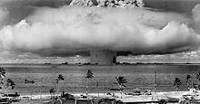 Champignon nucléaire s'élevant au-dessus de l'océan. Des navires se trouvent à proximité.