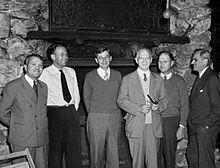 Six hommes debout et souriants.