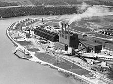Vue aérienne d'une usine avec trois cheminées au bord d'une rivière.