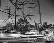 Hommes rassemblés autout d'une large structure en forme de derrick, un large objet rond est en train d'être soulevé.