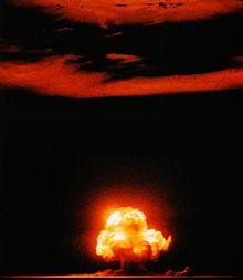 Explosion au niveau du sol et début de la formation d'un champignon atomique. Les nuages et le sol sont illuminés par la couleur orange de l'explosion.