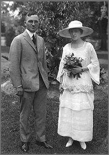 Wedding photo of Truman in gray suit and his wife in hat with white dress holding flowers