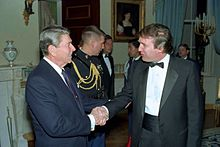 Trump shaking hands with President Ronald Reagan in 1987. Both are standing and facing each other.