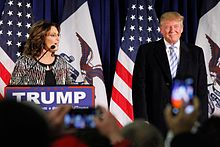 """Donald Trump with former Alaska governor Sarah Palin in January 2016. Palin is standing on the left side of the image, behind a podium with a sign that has the word """"TRUMP"""" in white-on-blue text. Trump is standing on the right side of the image. There are American flags hanging on poles behind them and the outlines of an audience in front of them."""