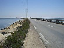 Perspective sur une route aménagée sur une digue entourée de part et d'autre par la mer; un pipeline a été aménagé du côté droit.