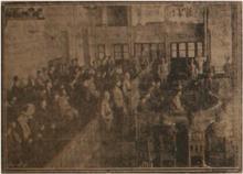Dans un tribunal, des hommes assis et quelques-uns debout, du côté du public ou des accusés.