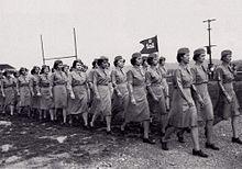 Un groupe de femmes en uniforme défile. Elles portent un petit étendard avec le symbole du corps des ingénieurs; un château surmonté de la lettre D.