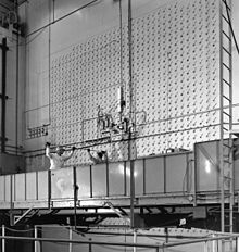 Deux ouvriers sur une plateforme mobile semblable à celle utilisée par les laveurs de vitres, poussent une tige dans l'un des nombreux petits orifices du mur en face d'eux.