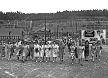 Travailleurs, essentiellement féminins, quittant un ensemble de bâtiments.