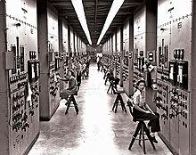 Un long couloir dans lesquelles des femmes assises sur des tabourets hauts surveillent des consoles avec des cadrans et des interrupteurs.