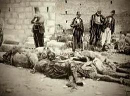 Corps alignés au pied d'un mur, des hommes debout les observent.