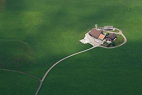 photo aérienne d'une exploitation agricole composé de 3 bâtiments, la photo donne l'impression que l'exploitation est une île au milieu d'une mer verte