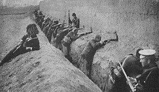 Des hommes debout dans une tranchée, dirigeant des fusils à travers une muraille.
