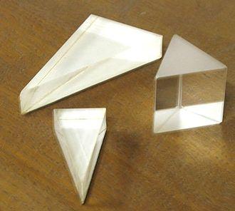 Photographie de trois prismes en verre posés sur une table en bois.
