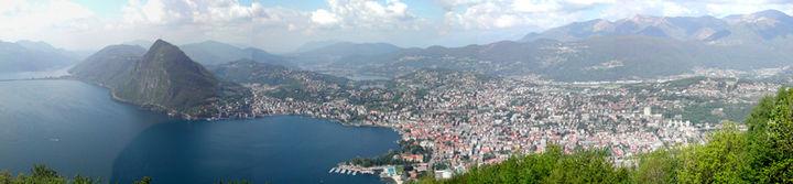 Photo panoramique de Lugano prise de «Monte brè» montrant à gauche: le lac, puis le «Monte San SAlvatore» qui marque l'entrée dans la crique autour de lqauelle s'étend la ville de Lugano